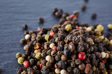 Top view on black, red and white peppercorns isolated on dark background, shallow depth of field.