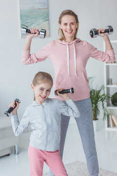 healthy mother and daughter working out with dumbbells at home
