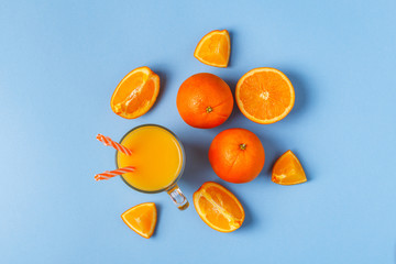 Oranges and juice on a blue pastel background