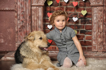 little girl with a big dog mongrel by the fireplace