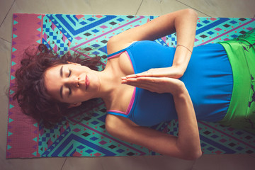 young yoga woman lying on mat with hands in namaste gesture above view