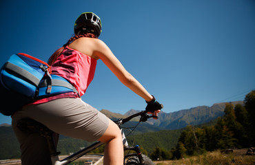 Image of woman in helmet on mountain-bicycle