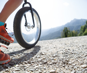 Photo of girl in sneakers on bicycle at road