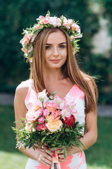 Beautiful young girl in wreath of flowers on her head and bouquet on green background