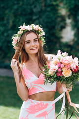Beautiful young smiling girl in wreath of flowers on her head touching hair with bouquet on green background