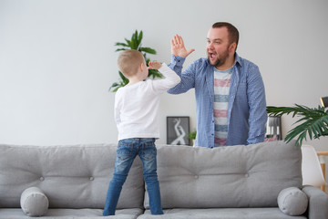 Family picture of young son standing on couch doing handshake with dad