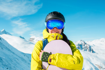 Photo of sporty woman wearing helmet and snowboarding against background of snowy hills