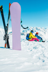 Photo of snowboard, skis on background of sitting sports woman and man on snowy hill