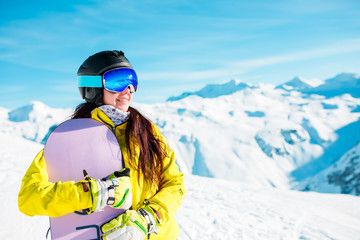 Image of smiling brunette wearing helmet and mask with snowboard on background of snowy hills