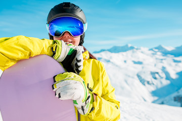 Portrait of smiling girl in helmet and mask with snowboard on background of snowy hills