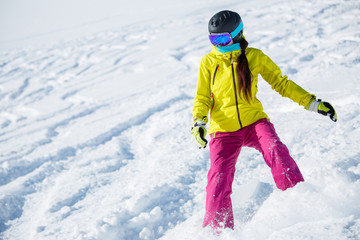 Photo of female brunette wearing helmet and mask, snowboarding from snowy mountain slope