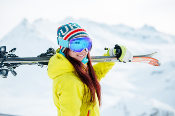 Image of smiling woman in mask with skis on her shoulder