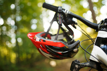 Image of bicycle with helmet on steering wheel on blurred background