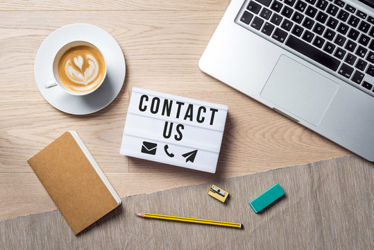 Contact us writing in lightbox lying on desk as flatlay