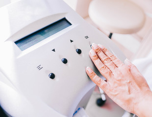 modern cosmetic apparatus for removing hair, the hand presses the buttons