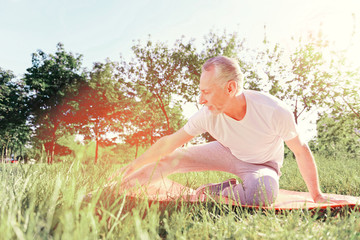 Sport and rest. Full length of smiling man sitting on the ground pad while doing useful stretching exercises