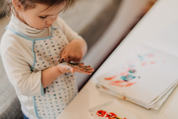 toddler girl in drawing apron draws fingers at home, close up of colored hands