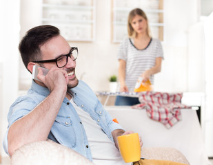 Husband resting on sofa while wife doing chores