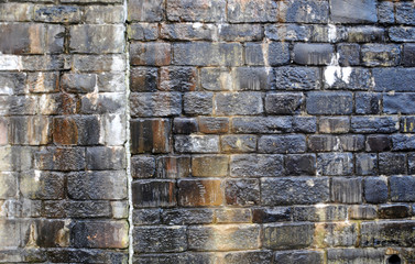 old irregular wet stone wall with damp marks and water streaks in shades of black and brown