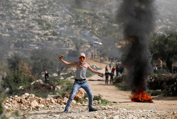 Palestinian demonstrator uses a sling to hurl stones at Israeli troops during clashes near Ramallah