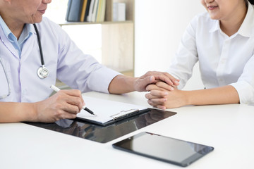 Friendly Professional medical doctor in white uniform coat holding patient hand sitting at the desk for encouragement, cheering and support while listen medical results