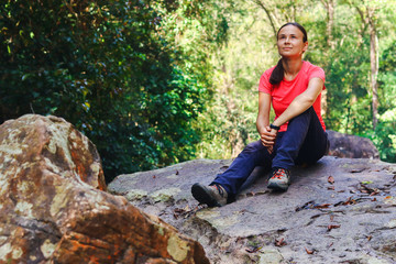 Tourist sit on dry waterfall stones