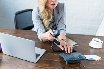 cropped image of businesswoman dialing number on stationary telephone