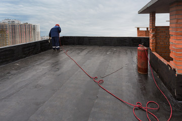 A worker puts waterproofing on the roof.