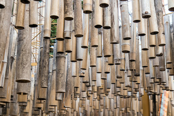 a bamboo sticks hang from the ceiling at outdoor constructions