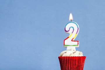 Number 2 birthday candle in a cupcake against a blue background