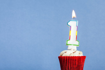Number 1 birthday candle in a cupcake against a blue background