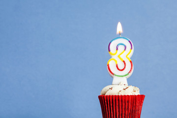 Number 3 birthday candle in a cupcake against a blue background