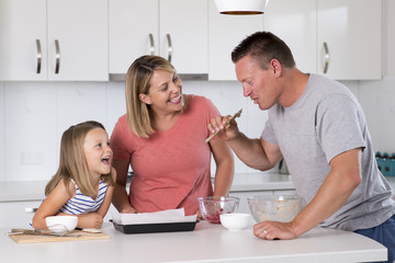 young happy couple baking together with little young beautiful daughter at home kitchen having fun playing with cream in family lifestyle