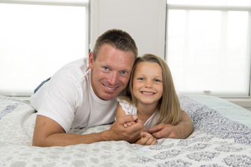 young man  lying on bed together with adorable 7 years old little girl playing happy at home in family father and daughter love lifestyle concept