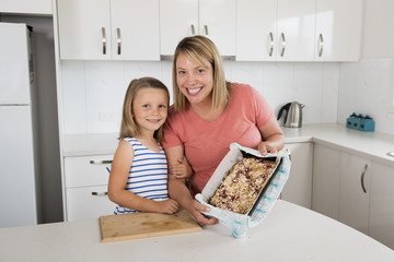 young mother and her sweet beautiful 7 years old daughter showing proud strawberry cake after baking together at home kitchen smiling happy