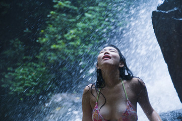 portrait of young beautiful Asian girl looking pure and enjoying nature beauty with face wet under amazing beautiful natural waterfall in tropical paradise