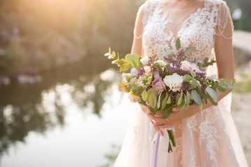 The bride in a beige wedding dress holding a lush bridal bouquet of lilac roses and a lot of greenery. Stylish wedding bouquet on the sunset background