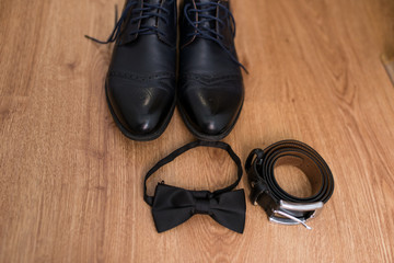 The groom's wedding accessories. Black leather belt, black necktie and black shoes on a wooden background.
