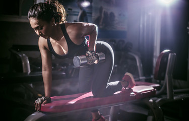 Strong woman lifting dumbbell in the fitness gym