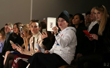 Members of the audience look on during the Fyodor Golan show at London Fashion Week, in London