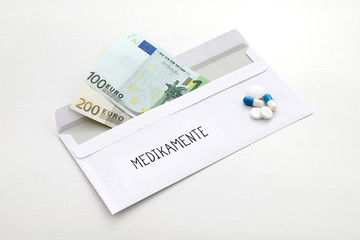 Umschlag mit Euroscheinen und der Aufschrift Medikamente und verschiedene Pillen nebenliegend