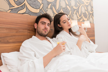 Attractive young couple in white robes, enjoying food and drink in bad after spa.Couple in relationship love and care