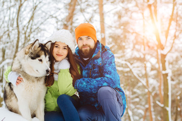 Family portrait of cute hipster couple in bright winter sportswear hugging with their alaskan malamute dog on the slope in winter forest. Pet lovers and freedom life style concept.