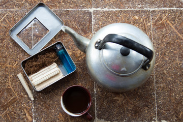 The lighter, coffee cup, tobacco and old pot put on the wood table.