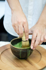 Hands stirring green tea powder