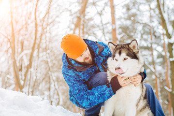 Cuty hipster beard man training , playing and hugging with his alaskan malamute dog on the slope in snowy winter forest.