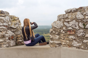 excited girl taking a picture on the castle wall, Ogrodzieniec, Poland