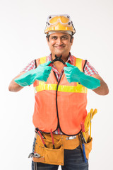 Indian handsome electrician engineer in actian, standing isolated over white background