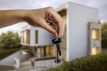 keys in hand, against a background of a blurred illustration modernist house, conceptual image