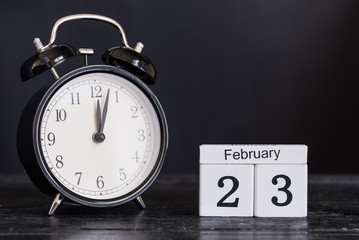 Wooden cube shape calendar for February 23 with black clock on black background. Copy space.